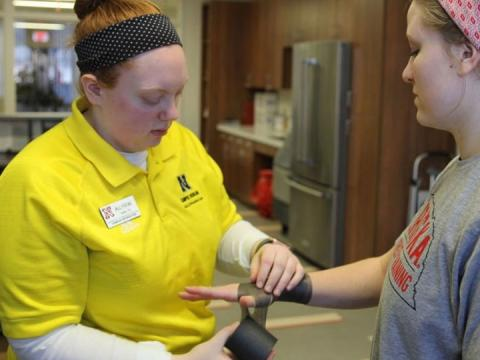 Athletic training student wraps the wrist of another student.