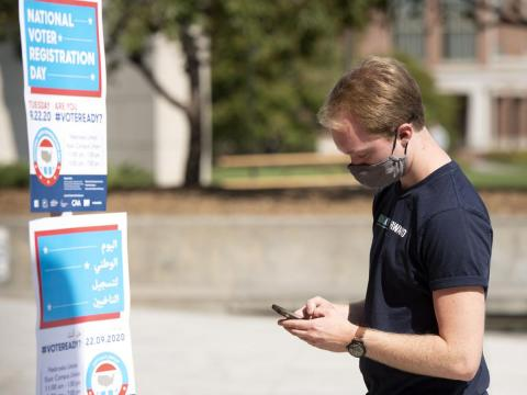 University of Nebraska-Lincoln junior Brent Lucke confirms his voter registration on vote.org after scanning a QR code on the sidewalk outside the Nebraska Union on Tuesday.