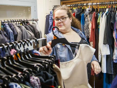 Alyssa Mettler, graduate assistant in the LGBTQA+ Resource Center, organizes clothes in the newly opened Lavender Closet.