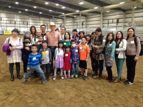 International students and family members visit with a cowboy to learn how the rodeo events work.