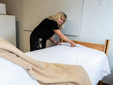 Mary Kavan, assistant facilities manager in Selleck Facilities Operations, prepares a bed inside Neihardt Hall. The university will begin using the Piper wing of Neihardt as a quarantine facility for its students.