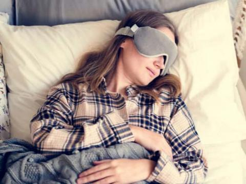 Woman sleeping in bed with mask