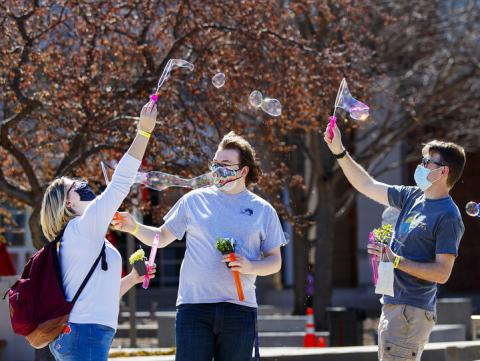 Students (from left) Samantha Moore, William Roarty and Jace Armstrong let the wind do the work as they blow bubbles outside the Nebraska Union during Spring Breakout on March 29. [Craig Chandler | University Communication]