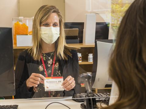 A pharmacist speaks with a UNL student about a medication at the University Health Center.