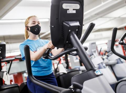 A female student exercises on an elliptical machine at the Campus Rec Center on the University of Nebraska-Lincoln campus.