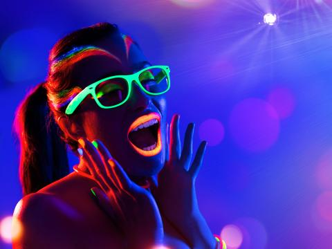 Woman screaming with glow-in-the-dark glasses.