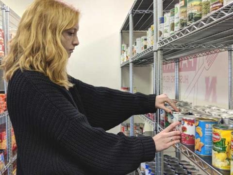 Sophomore Karin Ellefson arranges pantry donations during her volunteer shift at Huskers Helping Huskers Pantry+.