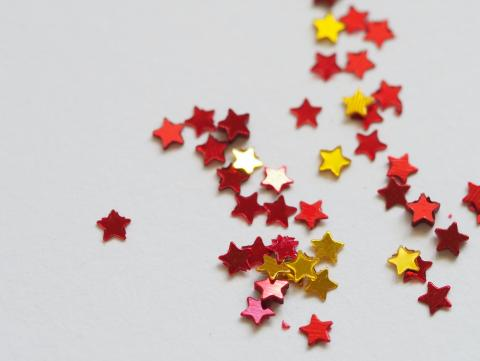 Red and gold star decorations lay on a white background.