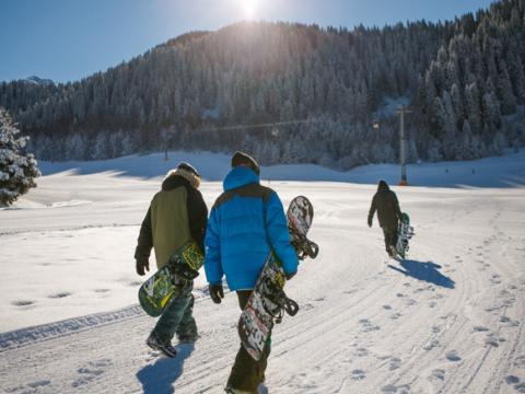 Three people carry snowboards towards a ski lift.